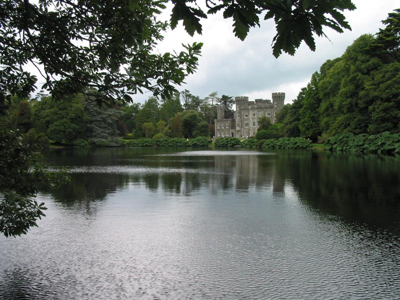 The photograph shows the front of Johnstown Castle and the lake is seen clearly in the foreground.  Trees in leaf frame the view of the castle.