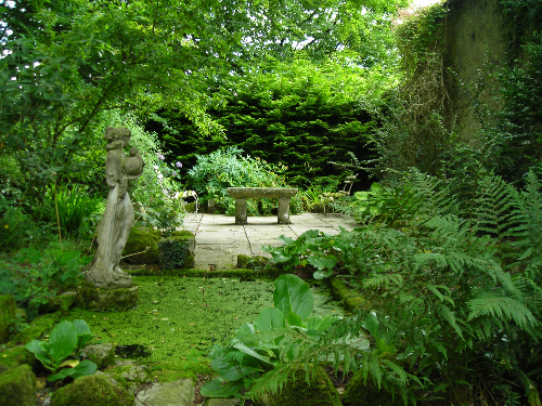 A photo showing a small garden with a statue, a seating area and a pool.