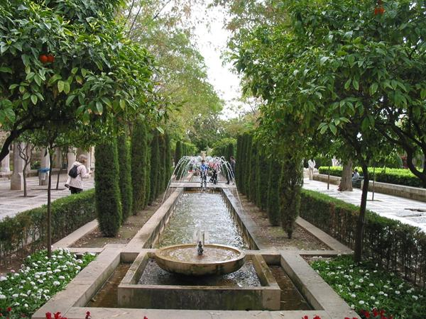 A formal garden showing fountains, water, walkways and planting.