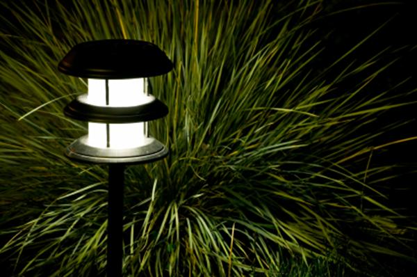 A photo of a garden lamp near some grasses.